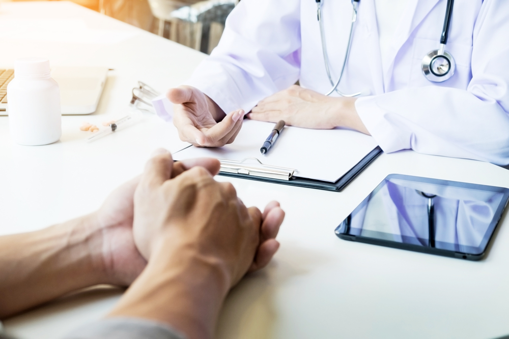 Hands of patient and doctor during consultation