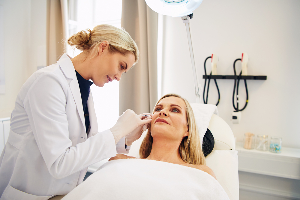 Smiling female doctor administers Botox injection to mature woman
