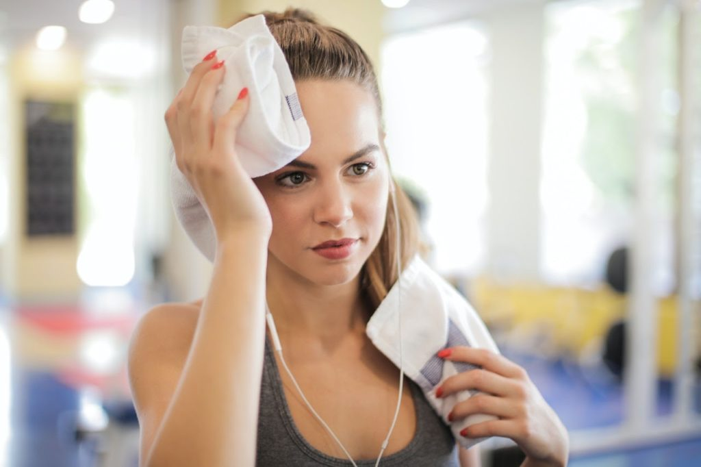 A Woman after completing an at-home workout from an article with tips for staying busy