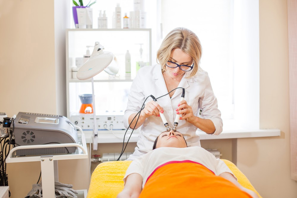 Female aesthetician providing cosmetic treatment to patient