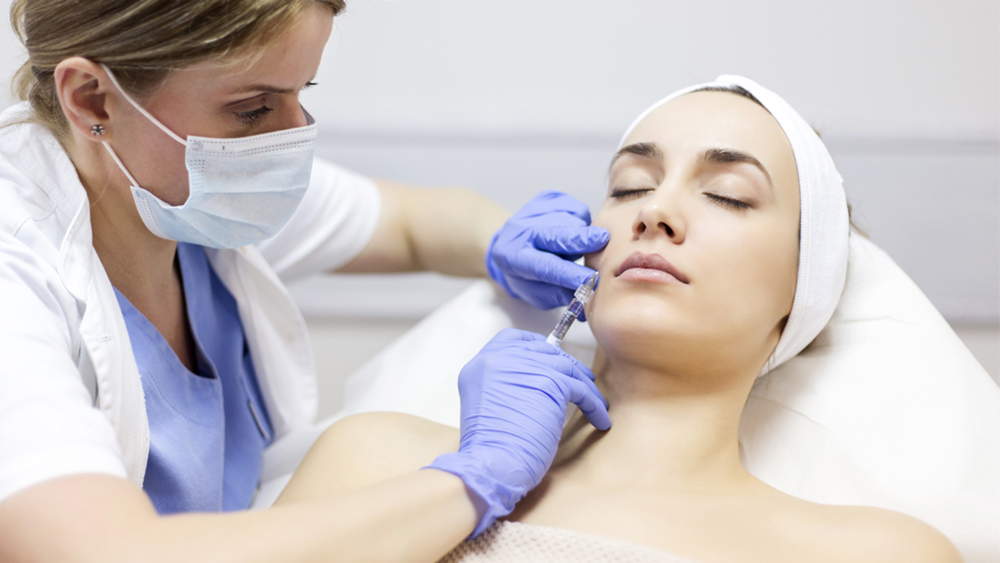 A woman gets an injection in her cheek