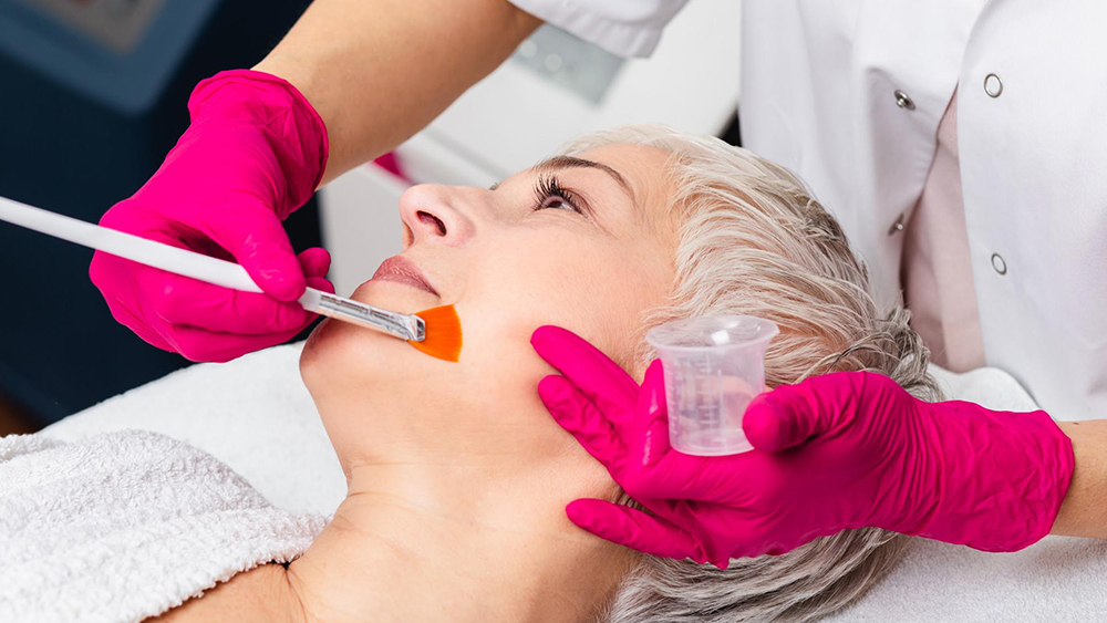 Cosmetic nurse applying a chemical peel on a patient