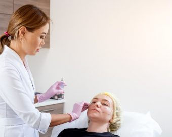 Female cosmetic injector giving Botox to a patient.